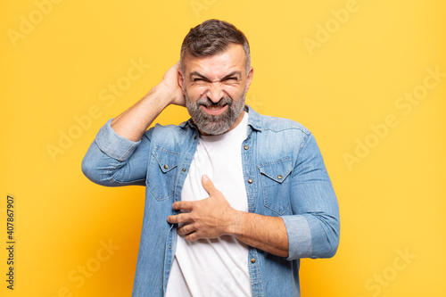 Obraz adult handsome man feeling stressed, frustrated and tired, rubbing painful neck, with a worried, troubled look - fototapety do salonu