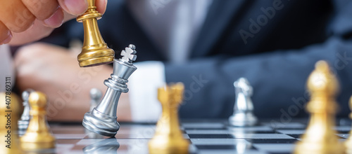 Fotomural businessman hand moving gold Chess King figure and Checkmate enermy or opponent during chessboard competition