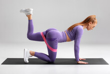 Fitness Woman Doing Kickback Exercise For Glutes With Resistance Band On Gray Background. Athletic Girl Working Out Donkey Kicks.