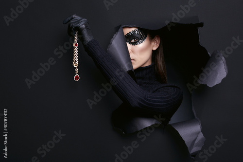 Fototapeta Elegant brunette woman in sequins mask posing with a stolen diamond necklace