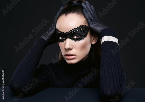 Fototapeta Elegant brunette woman in turtleneck sweater and sequins mask
