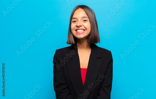 Fototapeta hispanic woman looking happy and goofy with a broad, fun, loony smile and eyes w