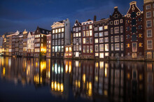 Amsterdam Canal At Night And Houses Reflected And Water.