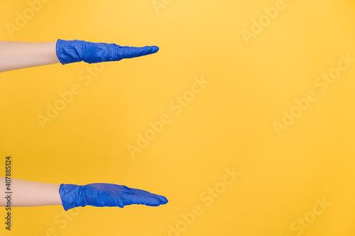 Billede på lærred Female hands in protective blue gloves shows width of something pretends holding item or thing, demonstrates size