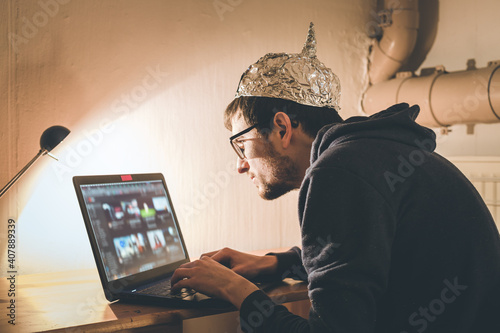 Foto Conspiracy theory concept: young man with aluminum cap searching the internet, s