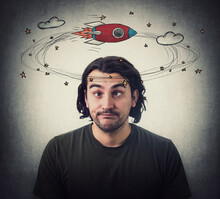 Silly Young Man Makes Funny Dumb Faces With Crossed Eyes. Body Language Emotional Reaction. Dizzy Daydreaming, Stars And Rocket Making Circles Around His Head. Guy Suffering From Strabismus