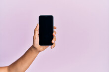 Hand Of Young Hispanic Man Showing Smartphone Over Isolated Pink Background.