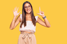 Young Hispanic Woman Wearing Casual Clothes And Glasses Showing And Pointing Up With Fingers Number Seven While Smiling Confident And Happy.