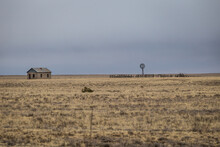 Windmill Surrounded By Vintage Wooden Fence Across From An Abandoned House In Open Yellow Pasture In Rural New Mexico