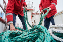 Two Male Colleagues Fishermans Pulling Rope On Deck Of A Boat