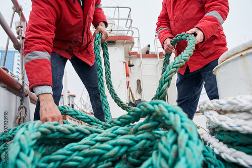 Canvas Print Two male colleagues fishermans pulling rope on deck of a boat