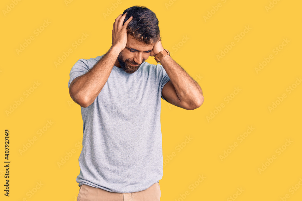 Fototapeta Young hispanic man wearing casual clothes suffering from headache desperate and stressed because pain and migraine. hands on head.