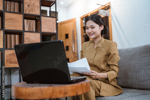 Fotografie, Obraz woman in government uniform holding papers while working from home online using
