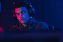 Shallow Focus Of A Hispanic Male Gamer With Headphones Streaming An Online Video Game