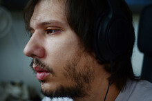 Young Attractive Male With Headphones On. Man With Facial Hair, Young Man Working On Computer With Over Ear Headphones On His Head.