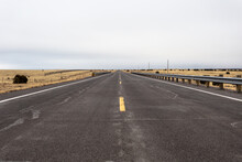 Low Angle View Of Two Lane Road Cutting Through Yellow Fields In Rural New Mexico On Cloudy Day