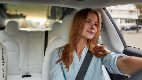 Fototapeta Portrait of young caucasian woman driving modern car