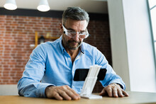 Mature Man Using Magnifying Glasses For Reading Small Text