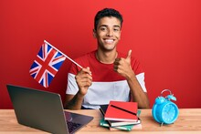 Young Handsome African American Man Exchange Student Holding Uk Flag Smiling Happy And Positive, Thumb Up Doing Excellent And Approval Sign