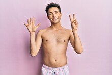 Young Handsome Man Wearing Swimwear Shirtless Showing And Pointing Up With Fingers Number Seven While Smiling Confident And Happy.