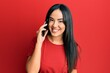 Leinwandbild Motiv Young beautiful hispanic girl having conversation talking on the smartphone looking positive and happy standing and smiling with a confident smile showing teeth