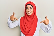 Young Beautiful Hispanic Girl Wearing Traditional Islamic Hijab Scarf Looking Confident With Smile On Face, Pointing Oneself With Fingers Proud And Happy.