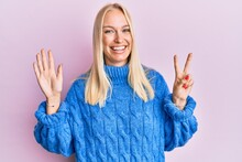 Young Blonde Girl Wearing Wool Winter Sweater Showing And Pointing Up With Fingers Number Seven While Smiling Confident And Happy.