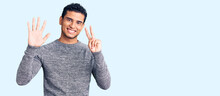 Hispanic Handsome Young Man Wearing Casual Sweater Showing And Pointing Up With Fingers Number Seven While Smiling Confident And Happy.