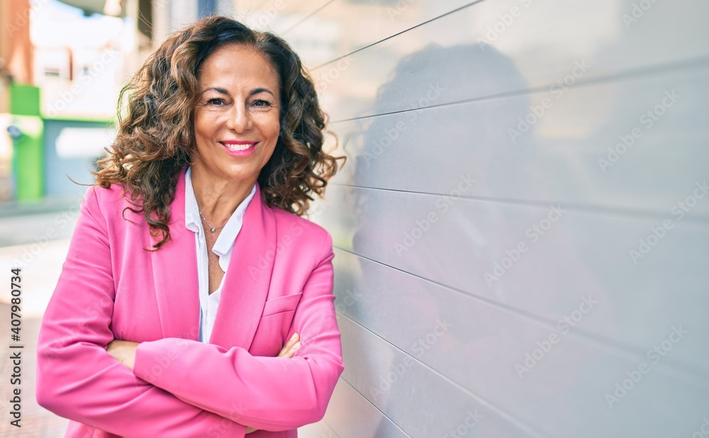 Fototapeta Middle age hispanic businesswoman smiling happy standing at the city.