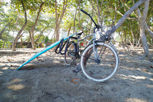 Blue Fish Surfboard And Bicycle On The Sandy Beach.