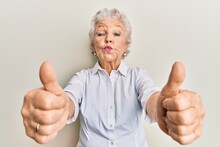 Senior Grey-haired Woman Doing Thumbs Up Positive Gesture Looking At The Camera Blowing A Kiss Being Lovely And Sexy. Love Expression.