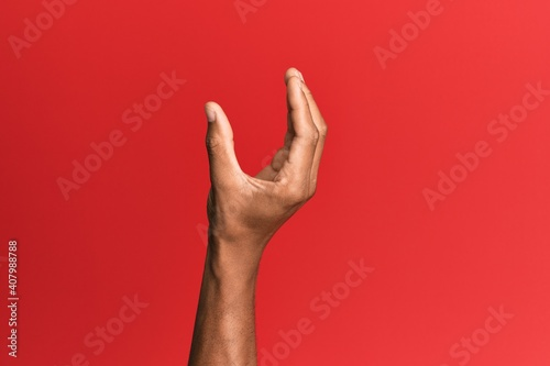 Fototapeta Hand of hispanic man over red isolated background picking and taking invisible t