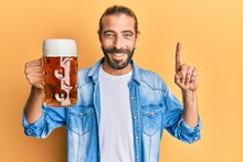 Attractive Man With Long Hair And Beard Drinking A Pint Of Beer Surprised With An Idea Or Question Pointing Finger With Happy Face, Number One
