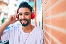 Young Arab Man Smiling Happy Using Headphones Leaning On The Wall At The City.