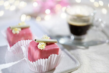 Valentine Petit Fours With Marzipan Icing And Cream Flowers. Espresso Coffee In Glass Cup. Garland Of Lights On Ivory, Off White Textile Tablecloth. Happy Valentine's Day