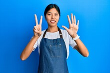 Young Chinese Woman Wearing Waiter Apron Showing And Pointing Up With Fingers Number Seven While Smiling Confident And Happy.