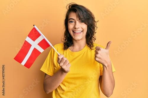 Ταπετσαρία τοιχογραφία Young hispanic woman holding denmark flag smiling happy and positive, thumb up d
