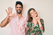 Beautiful Young Couple Of Boyfriend And Girlfriend Together Showing And Pointing Up With Fingers Number Seven While Smiling Confident And Happy.