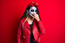Woman Wearing Day Of The Dead Costume Over Red Smelling Something Stinky And Disgusting, Intolerable Smell, Holding Breath With Fingers On Nose. Bad Smell