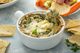 Fototapeta Kawa jest smaczna - Artichoke spinach dip in a baking dish with a cheese pull