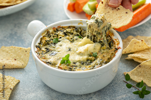Obraz Artichoke spinach dip in a baking dish with a cheese pull - fototapety do salonu
