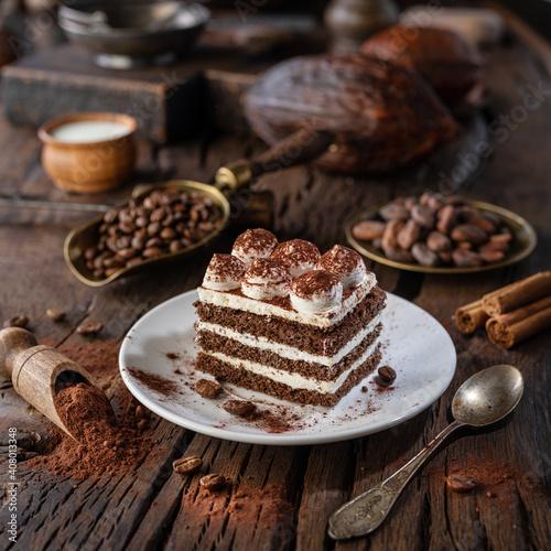 Obraz Slice of chocolate cake with tiramisu cream and cocoa powder on wooden table. - fototapety do salonu