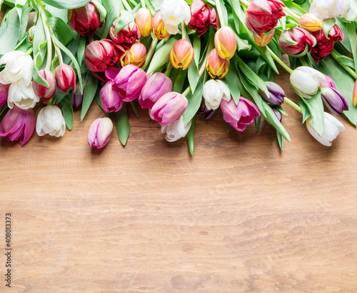 Foto Colorful  bouquet of tulips on wooden background.