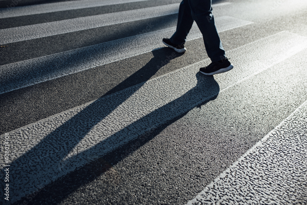 Fototapeta Man crossing on a pedestrian lane with his shadow on the street