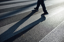 Man Crossing On A Pedestrian Lane With His Shadow On The Street