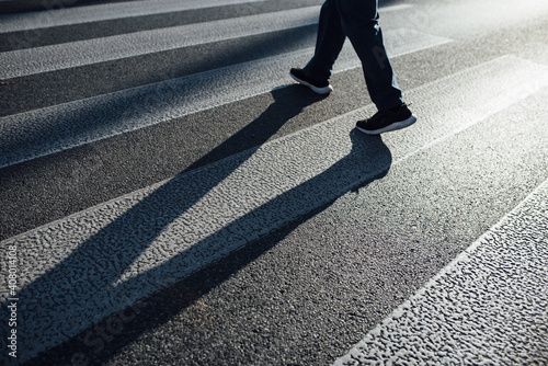 Canvastavla Man crossing on a pedestrian lane with his shadow on the street