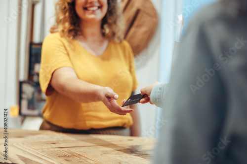 Fotografie, Obraz Customer paying by credit card to the saleswoman