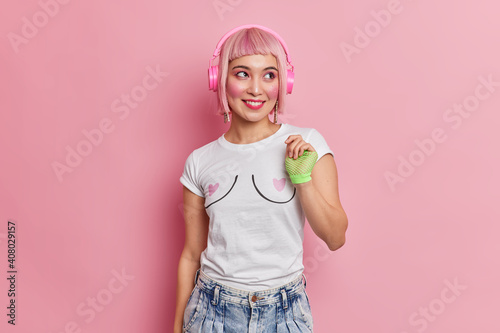 Fotografia Horizontal shot of happy teenage girl with pink hairstyle listens favorite music via headphones dressed in casual t shirt and jeans looks gladfully aside poses indoor