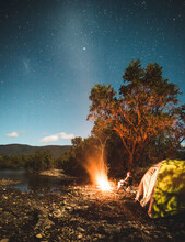 Man Sitting Near The Campfire By The Lake Under The Starry Night Sky
