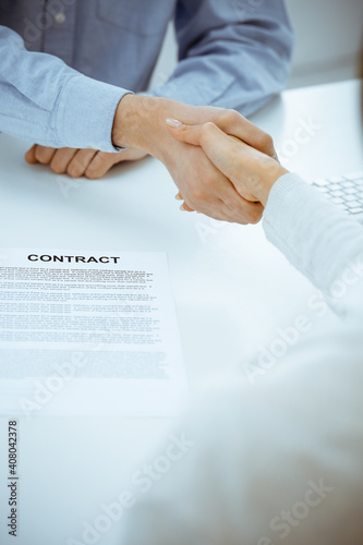 Casual dressed businessman and woman shaking hands after contract signing in white colored office. Handshake concept